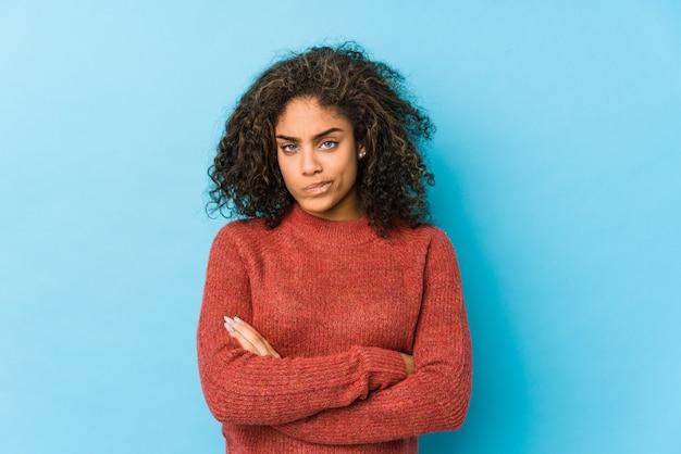 Młoda afroamerykanin kręcone włosy kobieta marszcząc brwi twarz z niezadowoleniem, trzyma założone ręce.