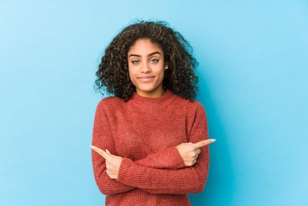 Młoda afroamerykanin kręcone włosy kobieta wskazuje na boki, próbuje wybrać jedną z dwóch opcji.