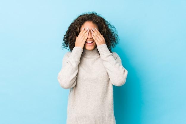 Młoda afroamerykanin kręcone włosy kobieta zakrywa oczy dłońmi, uśmiecha się szeroko czekając na niespodziankę.