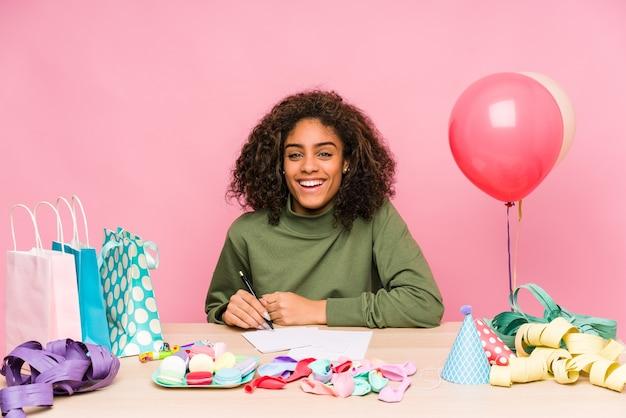 Młoda afroamerykanin planuje urodziny, śmiejąc się i bawiąc się.