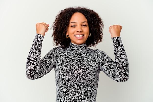 Młoda afroamerykanin rasy mieszanej kobieta na białym tle doping beztroski i podekscytowany. koncepcja zwycięstwa.