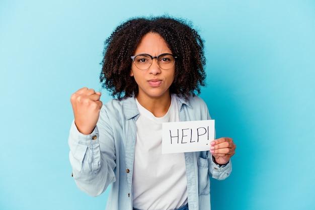 Młoda Afroamerykanin Rasy Mieszanej Kobieta Trzyma Koncepcję Papieru Pomocy Pokazując Pięść Do Kamery, Agresywny Wyraz Twarzy. Premium Zdjęcia