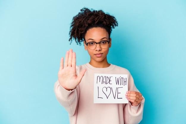 Młoda afroamerykanin rasy mieszanej kobieta trzyma koncepcję wykonane z miłością stojąc z wyciągniętą ręką pokazując znak stop, zapobiegając ci