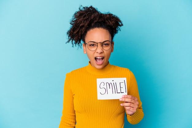 Młoda afroamerykanin rasy mieszanej kobieta trzyma pojęcie uśmiech krzyczy bardzo zły i agresywny.