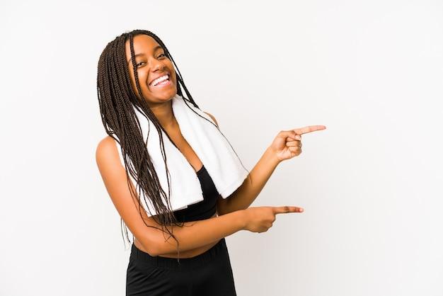 Młoda afroamerykanin sport kobieta na białym tle podekscytowany, wskazując palcami od hotelu.