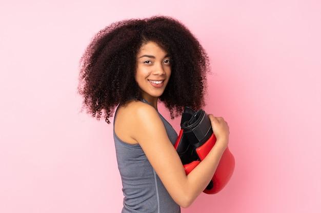 Młoda afroamerykanin sport kobieta na różowym tle z rękawic bokserskich