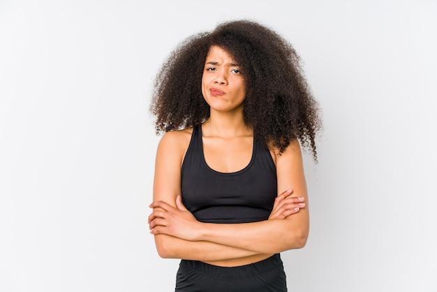 Młoda afroamerykanin sportowy kobieta marszcząc brwi z niezadowoleniem, trzyma założone ręce.