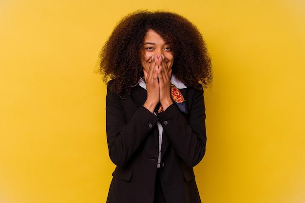 Młoda afroamerykanin stewardessa na żółto śmiejąc się z czegoś, zakrywając usta rękami.