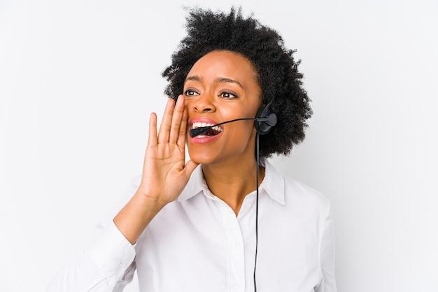 Młoda afroamerykanin telemarketer kobieta na białym tle krzycząc i trzymając dłoń w pobliżu otwartych ust.