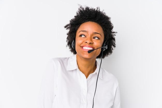 Młoda afroamerykanin telemarketer kobieta na białym tle marzy o osiągnięciu celów i celów