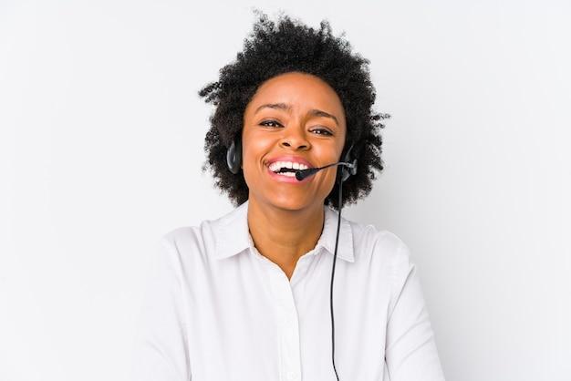 Młoda afroamerykanin telemarketer kobieta na białym tle śmiech i zabawę.
