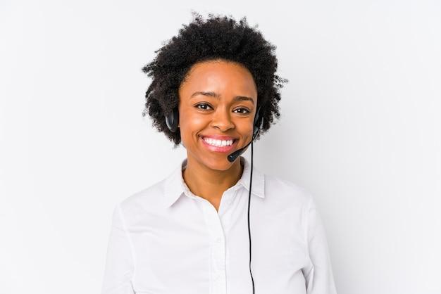 Młoda afroamerykanin telemarketer kobieta na białym tle szczęśliwy, uśmiechnięty i wesoły.