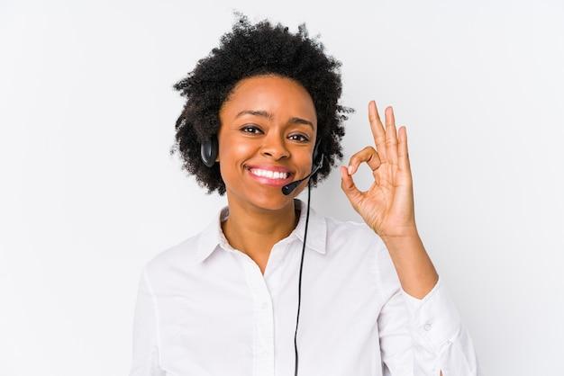 Młoda afroamerykanin telemarketer kobieta na białym tle wesoły i pewny siebie, pokazując ok gest.