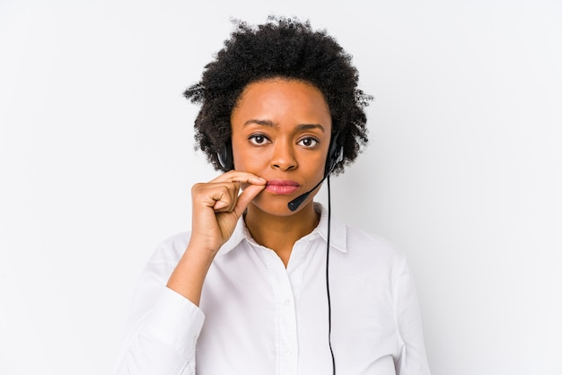 Młoda afroamerykanin telemarketer kobieta na białym tle z palcami na ustach, zachowując tajemnicę.