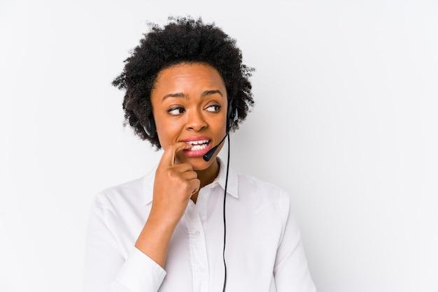 Młoda afroamerykanin telemarketer kobieta na białym tle zrelaksowany myślenie o czymś patrząc na przestrzeń kopii.