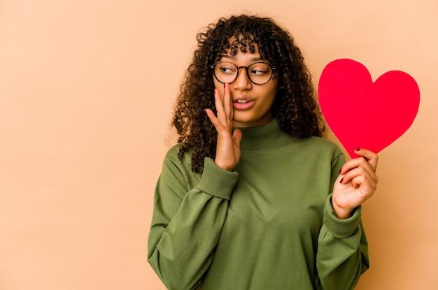 Młoda afroamerykanka afro kobieta trzyma serce walentynki mówi tajną gorącą wiadomość o hamowaniu i patrzy na bok