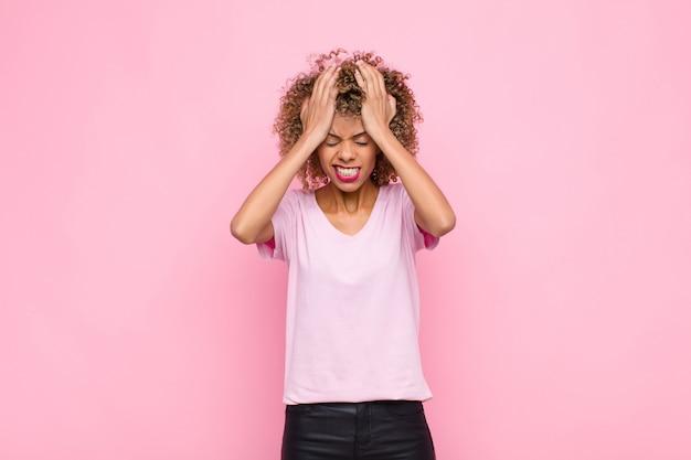 Młoda afroamerykanka czuje się zestresowana i niespokojna, przygnębiona i sfrustrowana bólem głowy, podnosząc obie ręce do różowej ściany