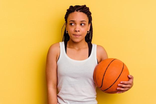 Młoda afroamerykanka gra w koszykówkę na białym tle na żółtej ścianie jest zdezorientowana, wątpliwa i niepewna