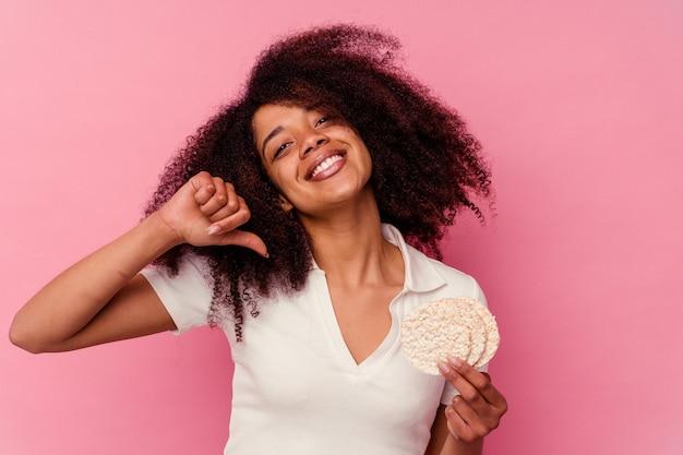 Młoda afroamerykanka jedząca ciastka ryżowe na różowym tle czuje się dumna i pewna siebie, przykład do naśladowania.