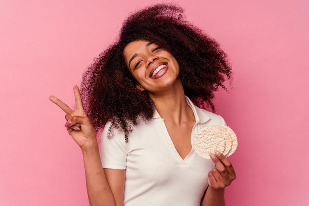 Młoda afroamerykanka jedzenie ciastek ryżowych na różowym tle radosna i beztroska pokazująca palcami symbol pokoju.