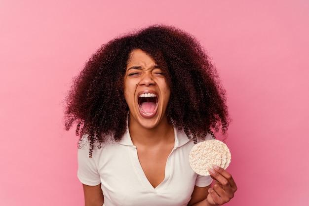 Młoda afroamerykanka jedzenie ciastka ryżowego na białym tle na różowym tle krzyczy bardzo zły i agresywny.