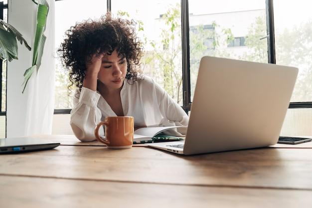 Młoda afroamerykanka jest zmęczona, wykończona ciężką pracą i nauką. znudzony i sfrustrowany patrząc na laptopa. głowa spoczywająca na dłoni. jasna przestrzeń duże okna. koncepcja domu. pojęcie stresu.