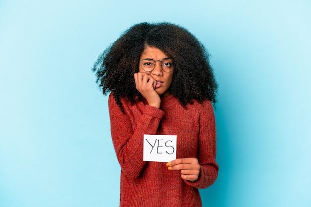 """Młoda afroamerykanka kręcona kobieta trzyma plakietkę """"tak"""", obgryzając paznokcie, nerwowa i bardzo niespokojna."""