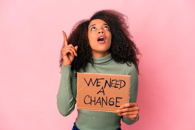 Młoda afroamerykanka kręcone kobieta potrzebujemy kartonu zmiany skierowanej do góry z otwartymi ustami.