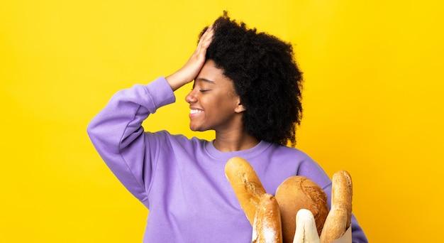 Młoda afroamerykanka kupująca coś na białym tle na żółtej ścianie coś sobie uświadomiła i zamierza rozwiązać problem