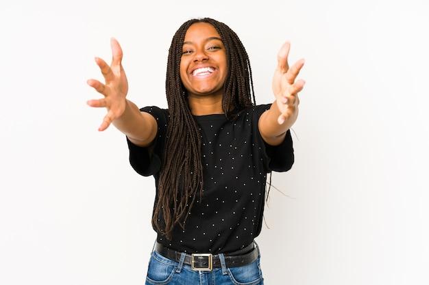 Młoda afroamerykanka na białym tle czuje się pewnie, przytulając aparat.