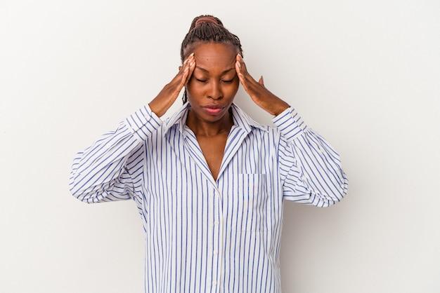Młoda afroamerykanka na białym tle dotyka świątyń i ma ból głowy.