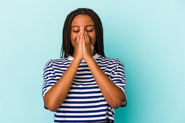 Młoda afroamerykanka na białym tle na niebieskim tle trzymając się za ręce w modlitwie w pobliżu ust, czuje się pewnie.