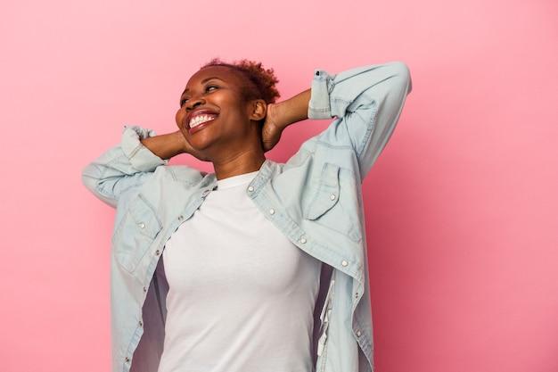 Młoda afroamerykanka na białym tle na różowym tle czuje się pewnie, z rękami za głową.