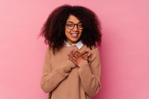 Młoda afroamerykanka na białym tle na różowym tle ma przyjazny wyraz, naciskając dłonią na klatkę piersiową. koncepcja miłości.