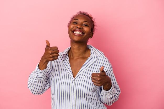 Młoda afroamerykanka na białym tle na różowym tle podnosząc oba kciuki do góry, uśmiechnięta i pewna siebie.
