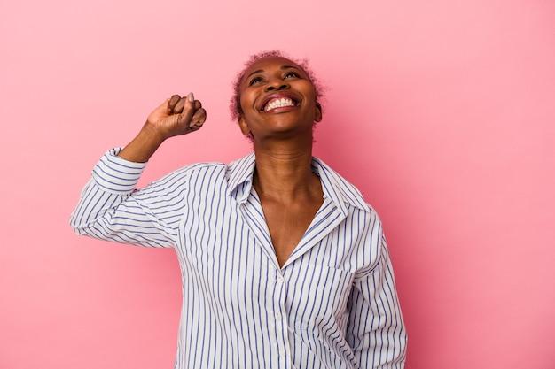 Młoda afroamerykanka na białym tle na różowym tle świętuje zwycięstwo, pasję i entuzjazm, szczęśliwy wyraz.