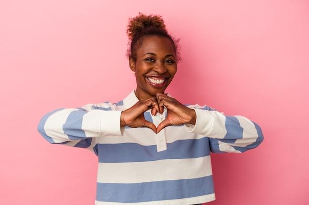 Młoda afroamerykanka na białym tle na różowym tle uśmiechając się i pokazując kształt serca rękami.