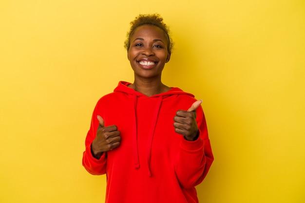 Młoda afroamerykanka na białym tle na żółtym tle podnosząc oba kciuki do góry, uśmiechnięta i pewna siebie.