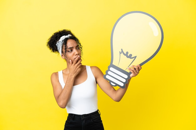 Młoda afroamerykanka na białym tle na żółtym tle trzyma ikonę żarówki i ma wątpliwości