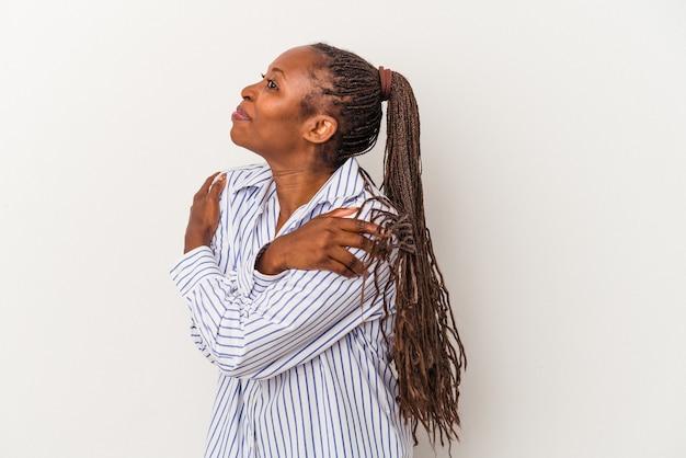 Młoda afroamerykanka na białym tle przytula się, uśmiechając się beztrosko i szczęśliwie.