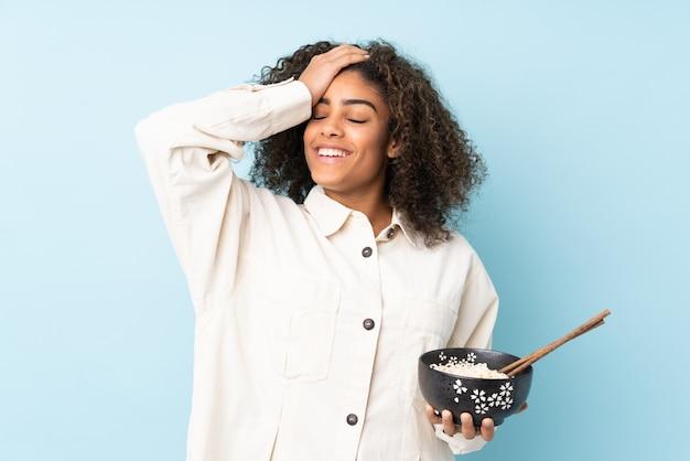 Młoda afroamerykanka na niebieskiej ścianie coś sobie uświadomiła i zamierza rozwiązać rozwiązanie trzymając miskę makaronu pałeczkami