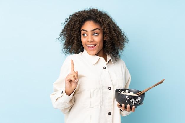 Młoda afroamerykanka na niebieskiej ścianie zamierza zrealizować rozwiązanie, podnosząc palec do góry, trzymając miskę makaronu pałeczkami