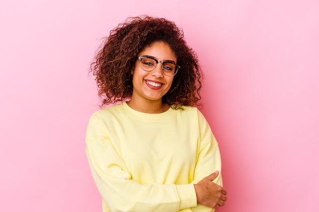 Młoda afroamerykanka na różowej ścianie, która czuje się pewnie, krzyżując ramiona z determinacją.