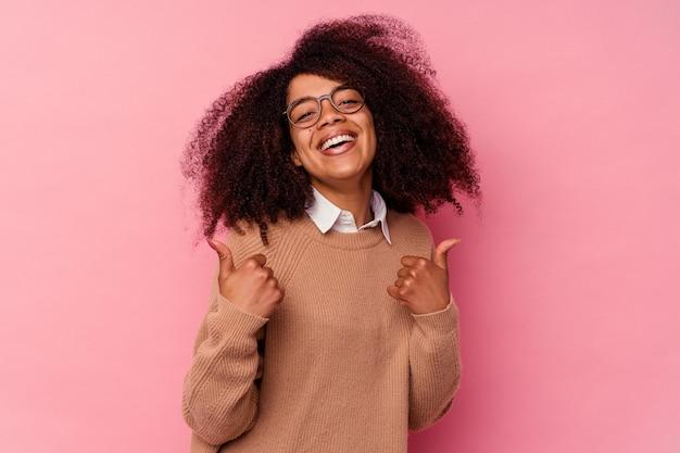 Młoda afroamerykanka na różowo podnosząca kciuki do góry, uśmiechnięta i pewna siebie.