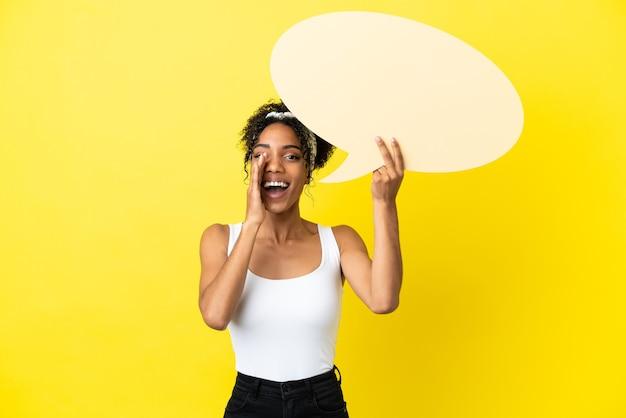 Młoda afroamerykanka na żółtym tle trzyma pusty dymek i krzyczy