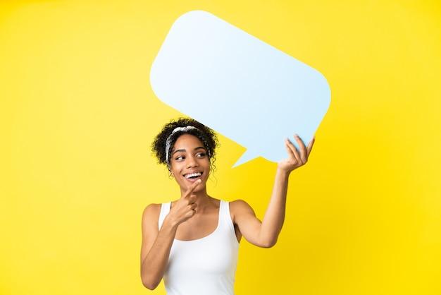 Młoda afroamerykanka na żółtym tle trzyma pusty dymek i wskazuje go