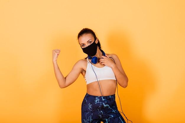 Młoda afroamerykanka nosząca odzież sportową i maskę medyczną, świętująca zwycięstwo i sukces bardzo podekscytowana z podniesionymi rękami, trenująca z hantlami