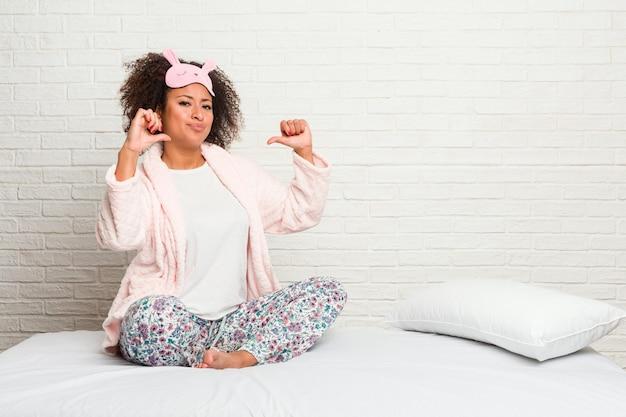 Młoda afroamerykanka nosząca pijama w łóżku czuje się dumna i pewna siebie.