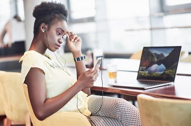 Młoda afroamerykanka o ciemnych kręconych włosach zastanawia się nad laptopem w kawiarni