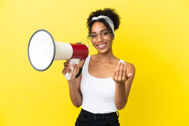 Młoda afroamerykanka odizolowana na żółtym tle trzymająca megafon i zapraszająca do przyjścia z ręką